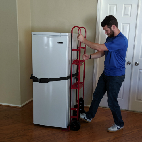 Moving Professional tightening the belt handle to secure an appliance to an appliance dolly