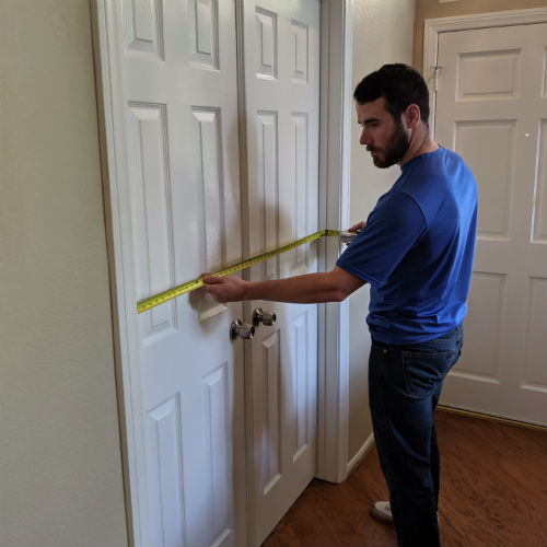 delivery professional using measuring tape to measure a set of french door