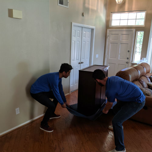 Delivery professionals sliding a cabinet across a wooden floor using a moving blanket
