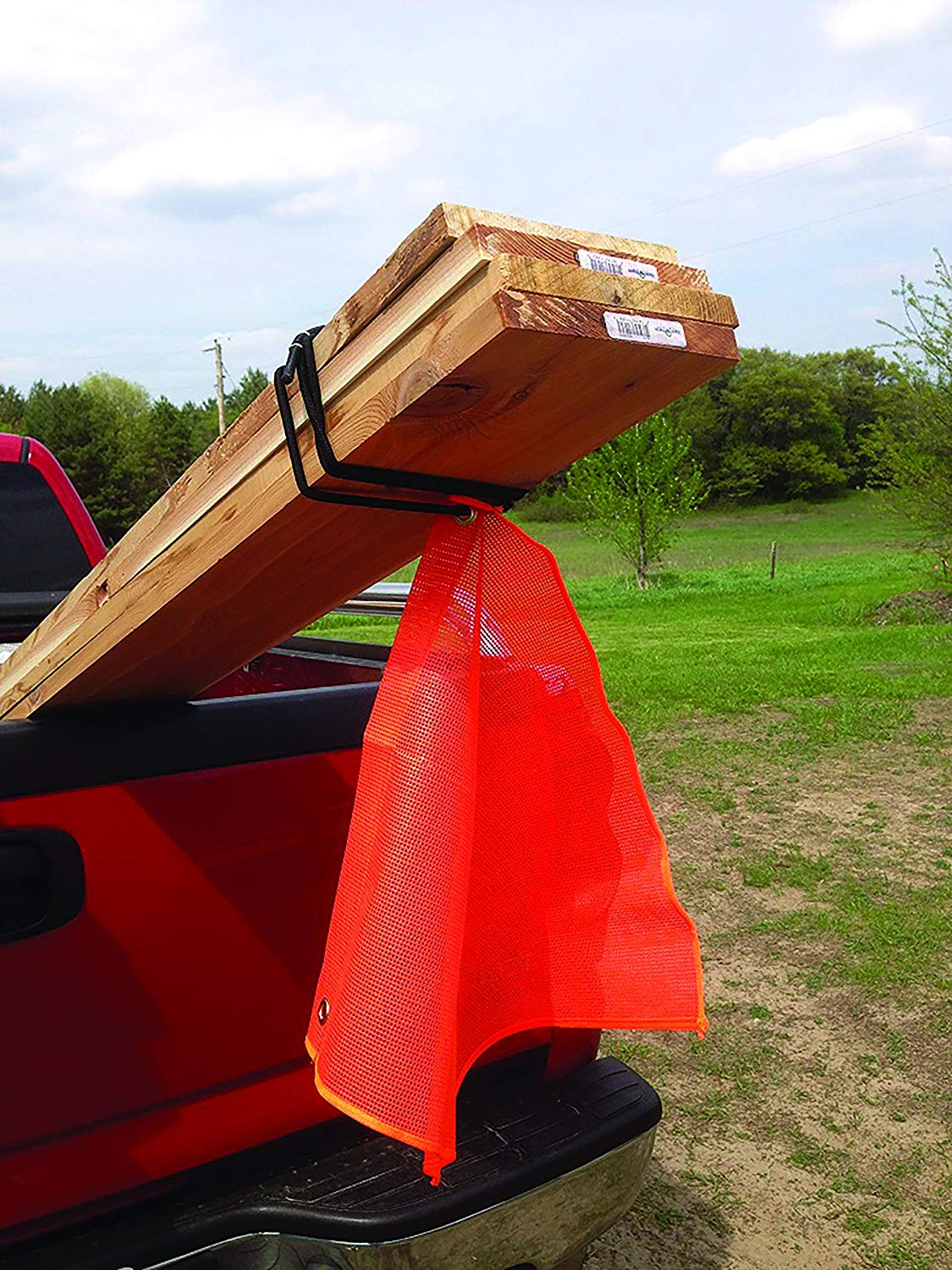 Lumber sticking out of the back of a truck with an orange safety flag attached