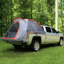 Rightline Gear Trunk Tent installed on the back of a silver pickup truck, parked in a wooded area